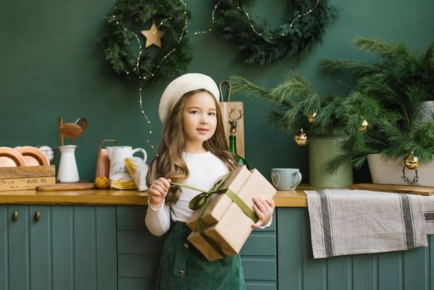 女の子は、クリスマスと新年のために飾られたキッチンの背景にエメラルドサテンリボンで結ばれたクリスマスプレゼントを保持しています。オープニングギフト