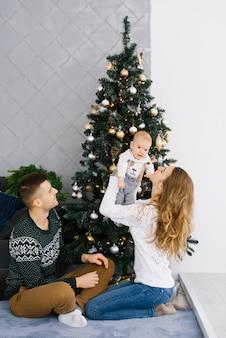 フレンドリーな若い家族:パパ、ママ、赤ちゃんがクリスマスツリーの近くに座っています。お母さんは赤ちゃんを腕の中で持ち上げて、彼に微笑んで、パパはそれらを見ます