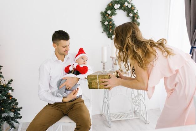 Младенец в костюме маленького санты на руках папы, а мама дарит ему рождественский подарок в гостиной, украшенной к празднику новый год