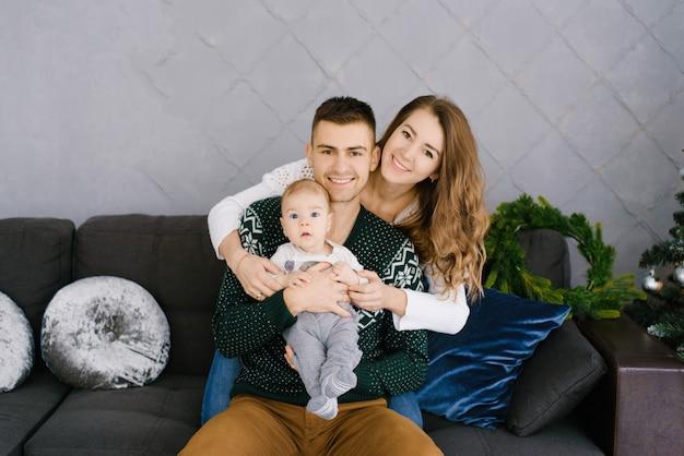 リビングルームで赤ちゃんを抱いて幸せな若い家族、クリスマスの装飾、ソファに座って笑顔