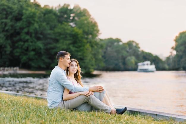 Молодая влюбленная пара, парень и девушка сидят на берегу озера, счастливые и улыбающиеся. первое свидание. день святого валентина