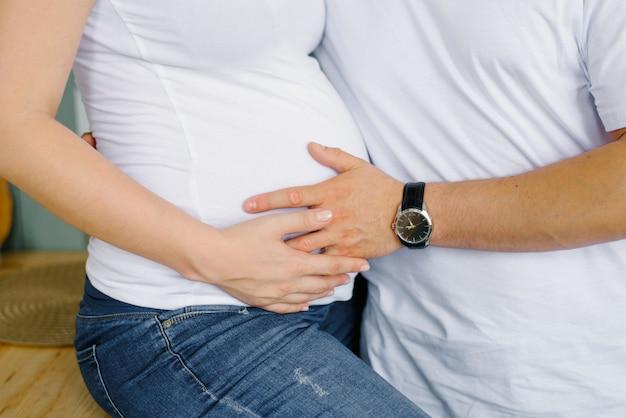 将来の父親は、妊娠中の妻である将来の母親の腹に手をかざします。赤ちゃんを待っている両親