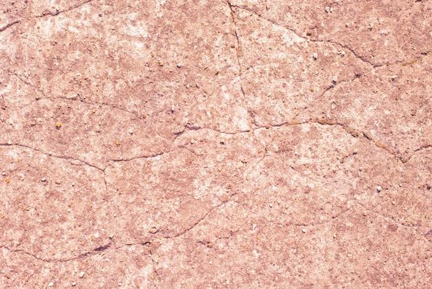 き裂を有する汚れたピンクの古い壁。テクスチャ。コピースペース