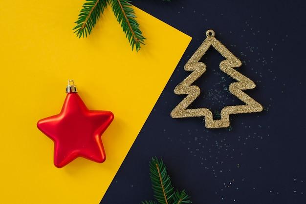 Творческая минималистская рождественская или новогодняя открытка. цветной двухцветный фон желтого и темно-синего цвета с блестками, на котором лежат красная ёлочная игрушка-звезда, золотая ёлка и еловые ветки