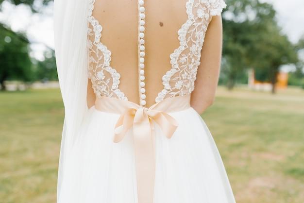 たくさんの白いボタンとサテンベージュの弓で美しい花嫁ドレスを開きます。結婚式の詳細