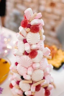 Елка из зефира, мармелада и сладостей на праздничном столе.