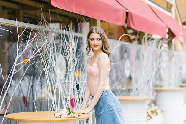 遠くを見て、夏の街を歩いて美しい若い女の子の肖像画。彼女の周りの美しい景色