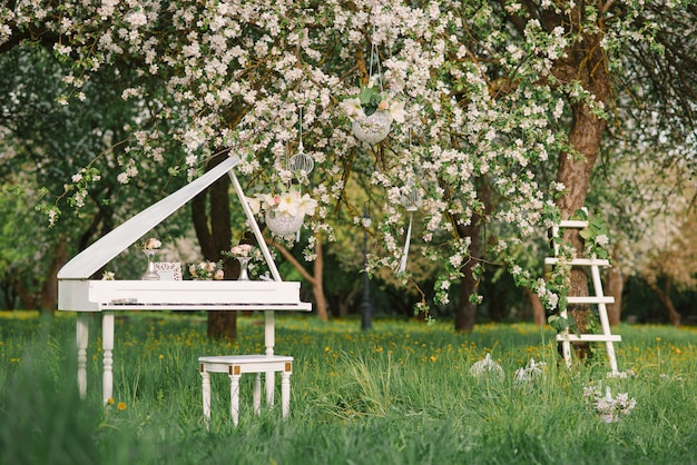 Белый рояль и белая лестница с романтическим декором весной в цветущем яблоневом саду