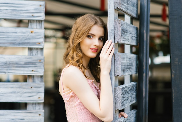 木製の門に立っているきれいで美しい少女の肖像画。唇に神秘的で魅惑的な笑顔