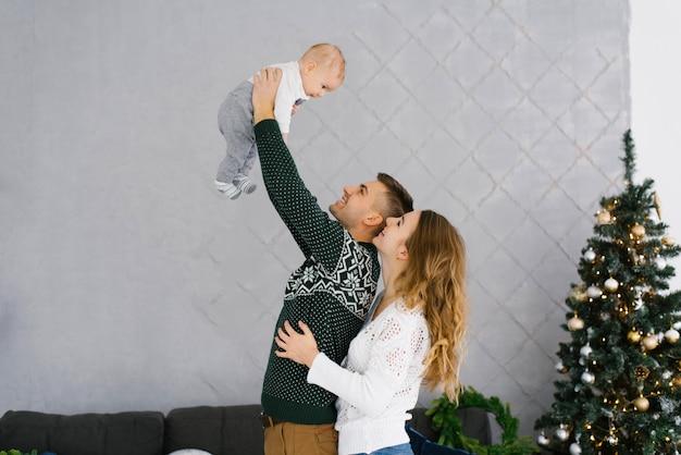 お父さんは幼い息子を腕で持ち上げ、お母さんはお父さんを抱きしめ、クリスマスツリーの近くで一緒に赤ちゃんを見ます