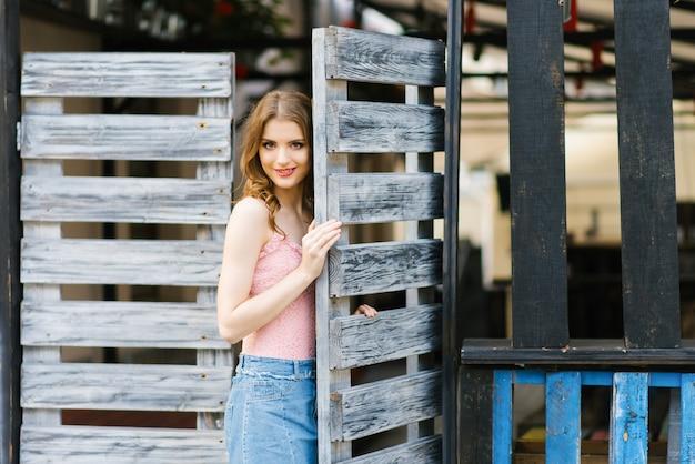 木製の門に立っているきれいで美しい少女の肖像画。新しい人生の概念、新しいものへの入り口、新しい扉が開かれました。コピースペース