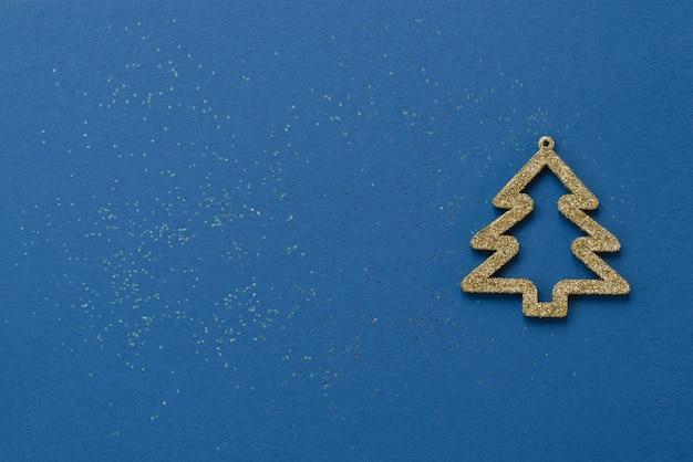 Творческая минималистская рождественская или новогодняя открытка. золото рождественская елка на синем фоне с блестками. скопируйте место для текста или приветствия