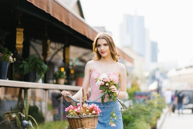 夕日を浴びて街の通りにきれいで美しい少女の肖像画。女の子はバラの花束を持ち、自転車のハンドルバーを持っています。夏の散歩のコンセプト