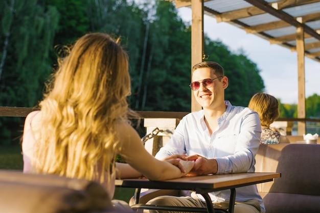 Парень и девушка на свидании сидят за столом в уличном кафе на озере. они счастливы и улыбаются