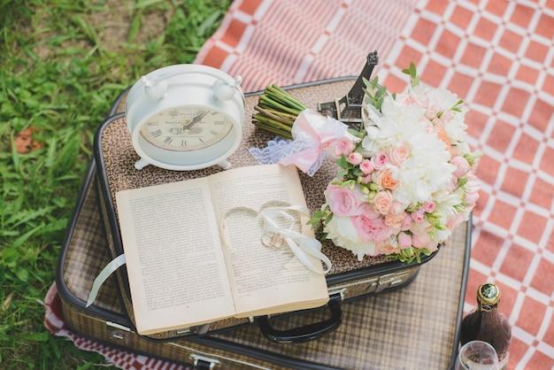 ロマンチックな結婚式の装飾:スーツケース、本、結婚指輪、置時計、ブライダルブーケ