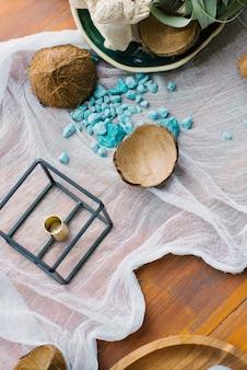 テーブルの装飾の壊れたココナッツと青い海の装飾的な石。海または熱帯の休日のテーマ