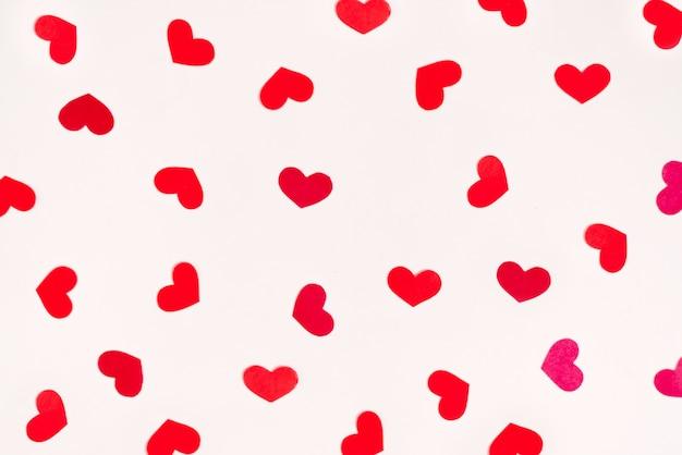 Красные сердца разбросаны в хаотическом порядке на белом фоне. открытка ко дню святого валентина
