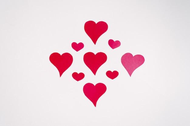 赤とピンクのハートは、図またはパターンに折り畳まれています。バレンタインのお祝いグリーティングカード
