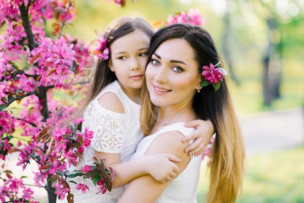 りんごの木の咲くバラ園で母と娘。幸せな母性。美しい家族の肖像画
