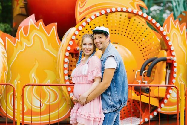 陽気な若い妊婦が赤ちゃんを待っています。背景の公園で明るい乗り物