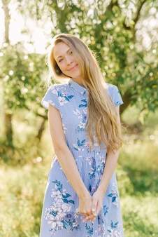 晴れた日に青いドレスの金髪少女の肖像画。甘くて優しい若いヨーロッパの女性