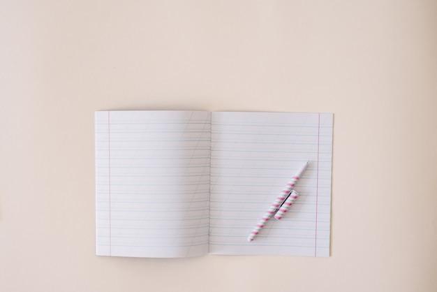 きれいなシーツとクラフトの背景にあるノートにペンがある定規で開いているノート。コピースペース