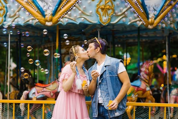 Пара в любви, поцелуи в мыльных пузырей в парках развлечений. день святого валентина