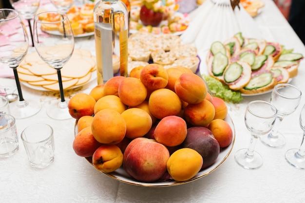 Свежие фрукты персики, абрикосы и сливы на тарелке на праздничном столе