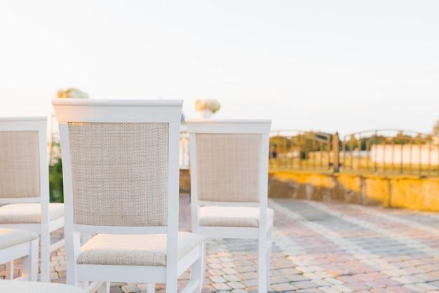 Три белых классических стула с бежевой обивкой на выездной свадебной церемонии. копирование пространства