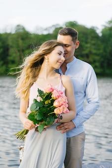 長い髪の少女と湖で抱き締める男と恋に若いカップル。女の子はピンクのバラを保持しています。バレンタインデーの最初のデート