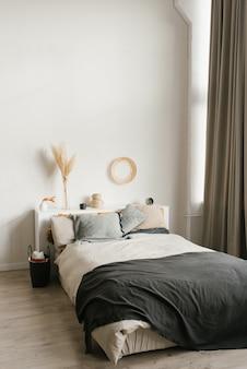 グレーと白の色調の寝室のダブルベッド。スカンジナビアの家のインテリア