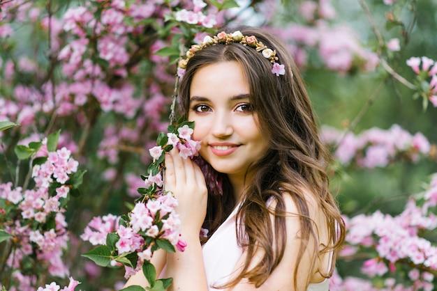 Красивая молодая симпатичная девушка с распущенными длинными волосами стоит возле цветущего весеннего куста вейгелы с розовыми цветами. она касается ветви своей рукой. профессиональный макияж