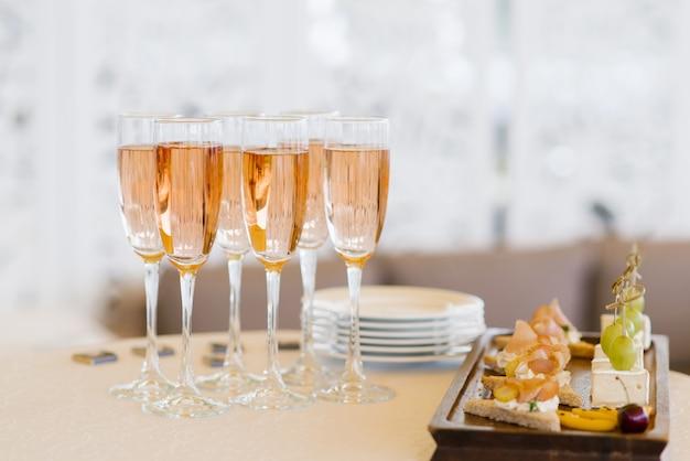 スナックとビュッフェテーブルにピンクのシャンパンのグラス