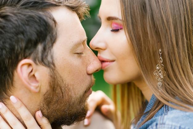 真の愛と優しさ。鼻にキス。愛の魅力的なカップルが屋外で時間を過ごす