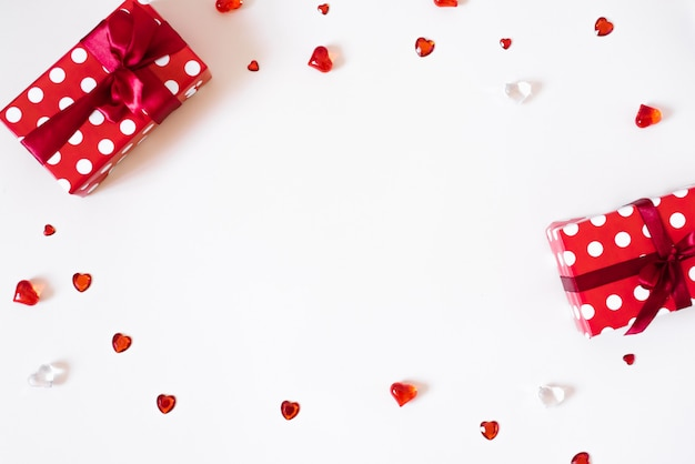 バレンタインデーの背景。明るい背景に弓、紙吹雪、ラインストーン、ガラスの心のギフト。バレンタインデーのコンセプト