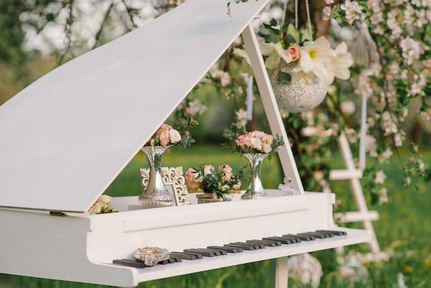 春の結婚式やロマンチックなディナーの装飾のデザインの装飾的な白いグランドピアノ