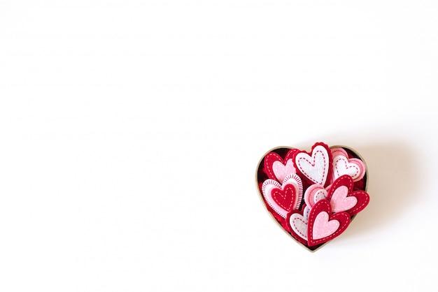 Картонная коробка в виде сердечка с разными сердечками внутри на свету