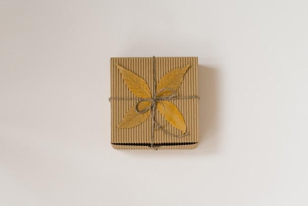 弓と秋の落ち葉で紐で結ばれたクラフトギフトボックス。秋に生まれた人への誕生日プレゼント。上面図