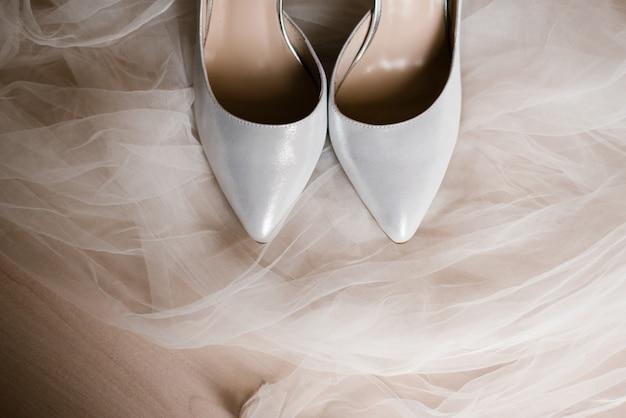 Серая женская обувь на белой тюлевой ткани