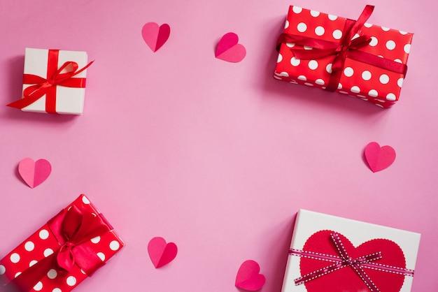 幸せなバレンタインデーのフレームの枠線。ギフトは、ホリデーペーパーとピンクの背景にピンクのハートに包まれています。