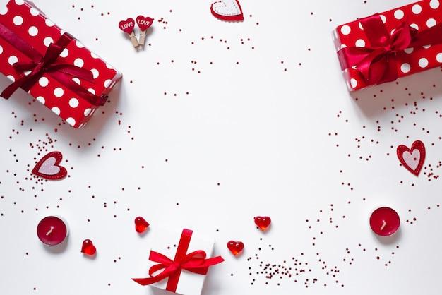 ギフト、紙吹雪、キャンドル、白い背景の上の心のフレーム。バレンタインデーの背景