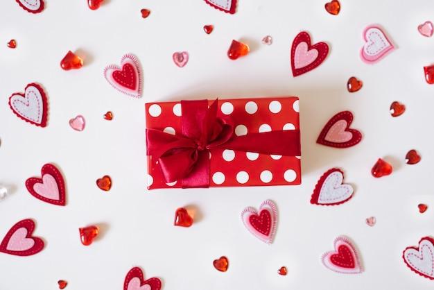 バレンタインデーの背景。赤いサテンリボンとたくさんの異なる心を持つ赤いギフトボックス