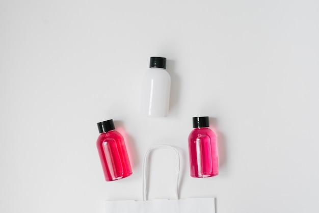 白い背景に白い紙のパッケージにシャワーやお風呂、白とピンクのボトルの化粧品のセット。