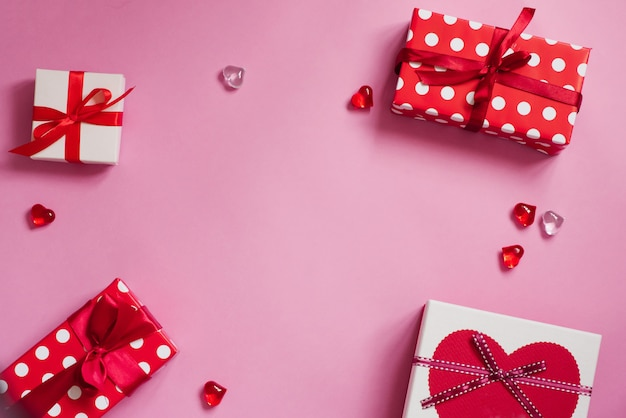 コピースペースとバレンタインの日。ピンクの背景のロマンチックな装飾のフレーム:ギフトボックスとガラスの心