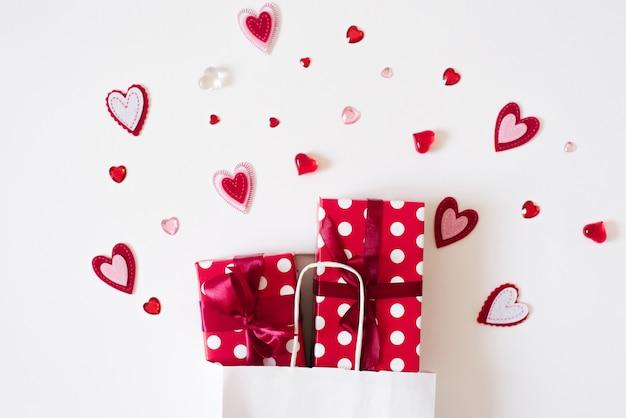 Подарочная сумка с подарками и сердца на белом фоне. концепция распродаж и скидок на день святого валентина