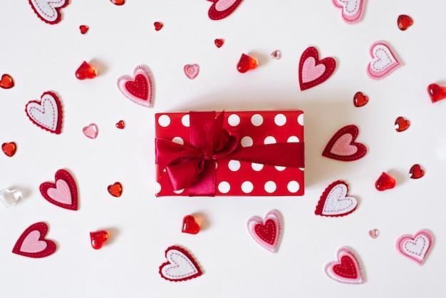 Подарок с красной атласной лентой и сердце на белом фоне. день святого валентина