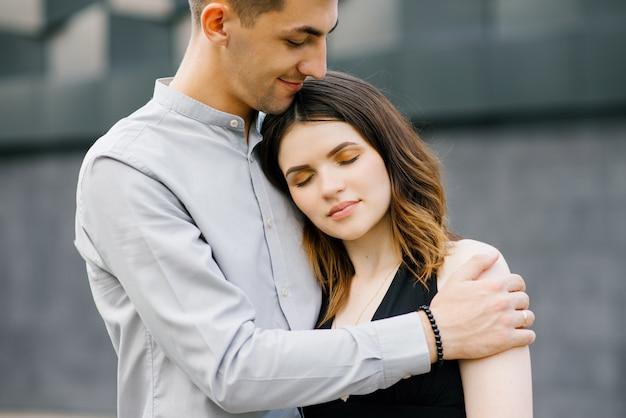 黒と白の服を抱いて愛の美しいカップル。少女は喜びで目を閉じた