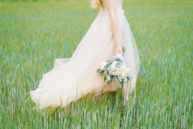 Красивый нежный свадебный букет в деревенском стиле с белой лентой в руках
