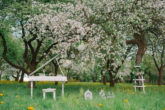 春に咲く庭で装飾的な白い脚立と白いグランドピアノ。ロマンチックな装飾