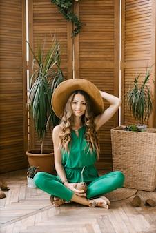 つば広の帽子と緑のジャンプスーツに身を包んだ美しい若い女性が座っていると笑顔